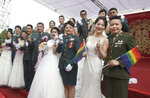 Two lesbian couples, from right to left, Yi Wang and Yumi Meng, Chen Ying-hsuan and Li Li-chen pose for a photo during a military mass weddings ceremony in Taoyuan city, northern Taiwan, Friday, Oct. 30, 2020. The two lesbian couples tied the knot in a mass ceremony held by Taiwan's military on Friday in a historic step for the island. Taiwan is the only place in Asia to have legalized gay marriage, passing legislation in this regard in May 2019.(AP Photo/Chiang Ying-ying)
