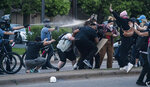 Police officers use pepper spray as they try to disperse people during a protest in Minneapolis on Sunday, May 31, 2020. Protests were held in U.S. cities over the death of George Floyd, a black man who died after being restrained by Minneapolis police officers on May 25. (Elizabeth Flores/Star Tribune via AP)