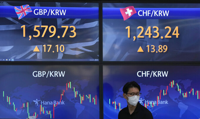 A currency trader walks near the screens showing the foreign exchange rates at the foreign exchange dealing room in Seoul, South Korea, Thursday, June 17, 2021. Asian stock markets followed Wall Street lower Thursday after the Federal Reserve indicated it might ease off economic stimulus earlier than previously thought.(AP Photo/Lee Jin-man)