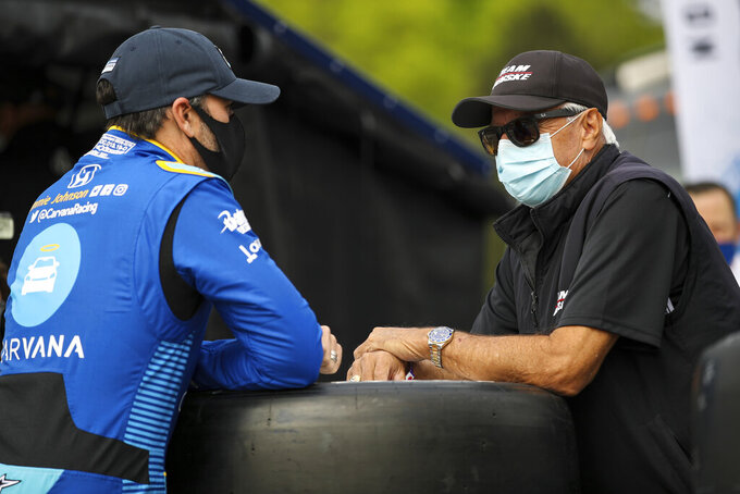 In this image provided by IndyCar, seven-time NASCAR champion Jimmie Johnson,left, speaks to four-time Indianapolis 500 winner Rick Mears before the first IndyCar practice session of the season, Saturday, April 17, 2021 at Barber Motorsports Park in Birmingham, Ala. Johnson will be an IndyCar rookie this season and make his series debut in Sunday's opener. Mears was his childhood hero. (Joe Skibinski/IndyCar via AP)