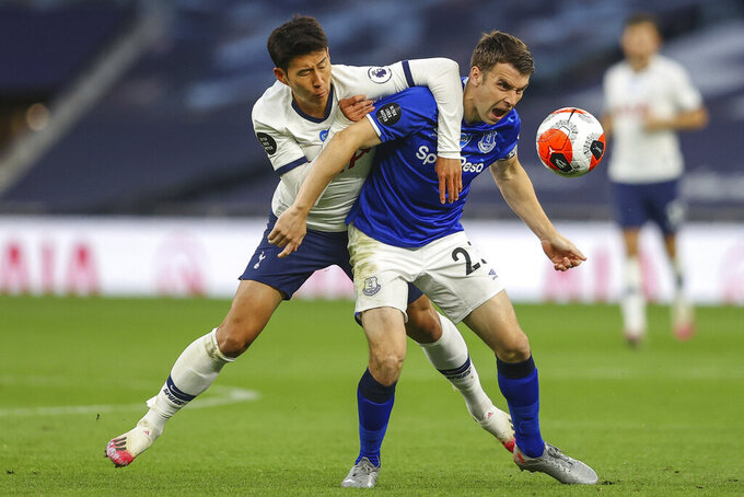 Tottenham's Son Heung-min, left, duels for the ball with Everton's Seamus Coleman during the English Premier League soccer match between Tottenham Hotspur and Everton FC at the Tottenham Hotspur Stadium in London, England, Monday, July 6, 2020. (Richard Heathcote/Pool via AP)