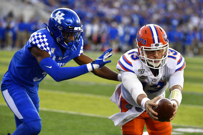 Florida quarterback Feleipe Franks (13) reaches for extra yards ahead of Kentucky safety Jordan Griffin (3) during the first half of an NCAA college football game in Lexington, Ky., Saturday, Sept. 14, 2019. (AP Photo/Timothy D. Easley)