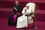 Pope Francis, flanked by Archbishop Georg Gaenswein, applauds in the Paul VI Hall at the Vatican during an audience with members of parish evangelization services, Monday, Nov. 18, 2019. (AP Photo/Alessandra Tarantino)