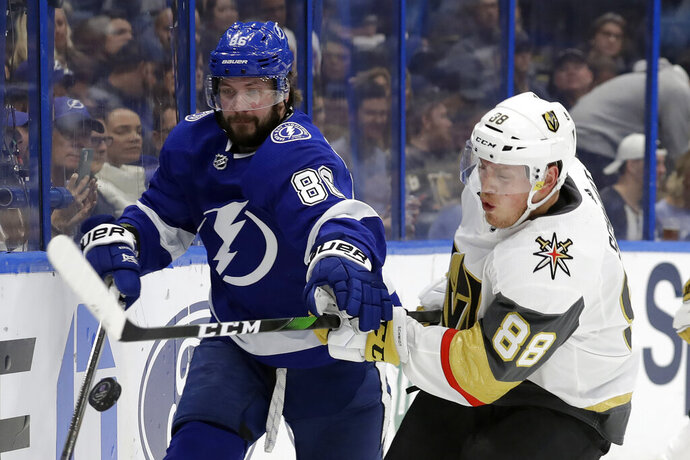 Tampa Bay Lightning right wing Nikita Kucherov (86) and Vegas Golden Knights defenseman Nate Schmidt (88) chase a bouncing puck during the second period of an NHL hockey game Tuesday, Feb. 4, 2020, in Tampa, Fla. (AP Photo/Chris O'Meara)