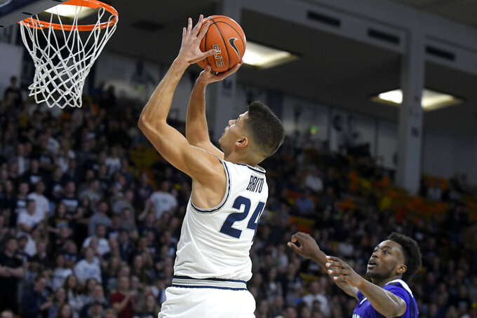 Utah State guard Diogo Brito (24) takes a shot as Weber State guard Kham Davis defends during the first half of an NCAA college basketball game Friday, Nov. 8, 2019, in Logan, Utah. (AP Photo/Eli Lucero)