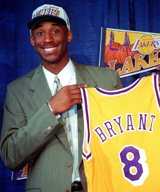 FILE - In this July 12, 1996 file photo Kobe Bryant, 17, jokes with the media as he holds his Los Angeles Lakers jersey during a news conference at the Great Western Forum in Inglewood, Calif. Bryant, a five-time NBA champion and a two-time Olympic gold medalist, died in a helicopter crash in California on Sunday, Jan. 26, 2020. He was 41. (AP Photo/Susan Sterner, file)