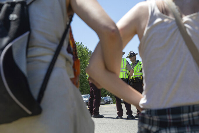 Activists lock arms as they occupy an Enbridge Line 3 pump station near Park Rapids, Minn., on Monday, June 7, 2021, as State Troopers, in background, direct traffic on Highway 71. (Evan Frost/Minnesota Public Radio via AP)