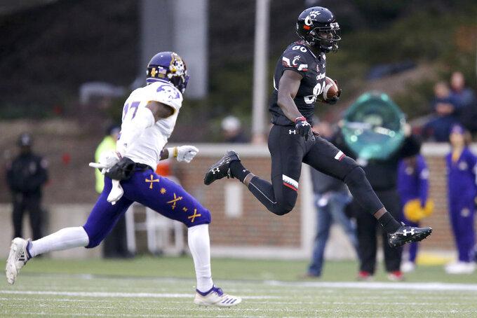 Cincinnati wide receiver Malick Mbodj (80) runs after making a catch as East Carolina defensive back Daniel Charles (27) closes in during an NCAA college football game, Friday, Nov. 23, 2018, in Cincinnati.   (Kareem Elgazzar/The Cincinnati Enquirer via AP)
