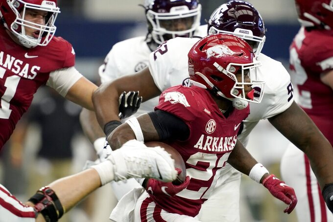 Arkansas running back Trelon Smith (22) carries the ball as Texas A&M defenders give chase in the first half of an NCAA college football game in Arlington, Texas, Saturday, Sept. 25, 2021. (AP Photo/Tony Gutierrez)