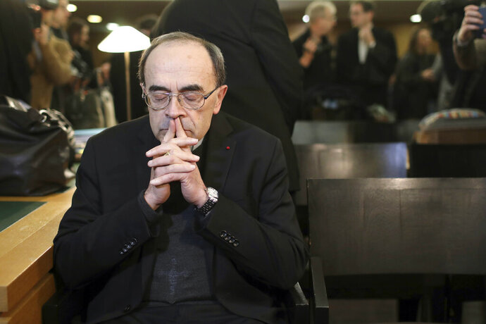 FILE - In this Jan. 7, 2019 file photo, French Cardinal Philippe Barbarin waits for the start of his trial at the Lyon courthouse, central France. Pope. A French court on Thursday March 7, 2019 is expected to acquit a cardinal and five other defendants accused of protecting a pedophile priest, but alleged victims say France's most important church sex abuse trial has at least allowed them to bring the affair into the open. (AP Photo/Laurent Cipriani, File)