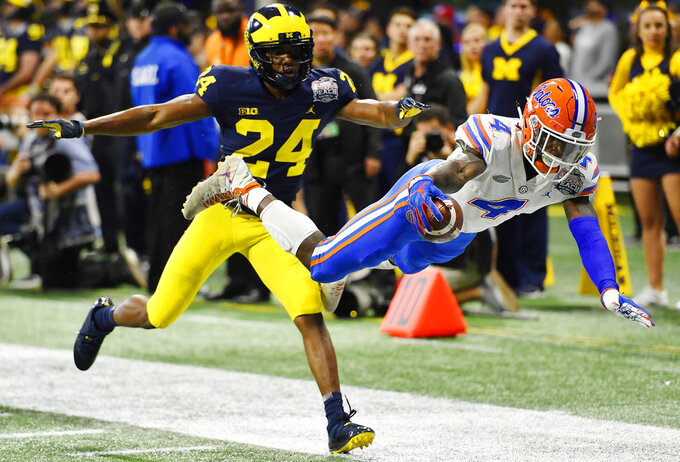 Florida running back Kadarius Toney (4) leaps toward the end zone against Michigan defensive back Lavert Hill (24) during the first half of the Peach Bowl NCAA college football game, Saturday, Dec. 29, 2018, in Atlanta. (AP Photo/Mike Stewart)