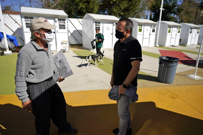 Hope of the Valley CEO Ken Craft, right, talks to resident Ted Beauregard outside of a row of tiny homes for the homeless, Thursday, Feb. 25, 2021, in the North Hollywood section of Los Angeles. (AP Photo/Marcio Jose Sanchez)