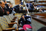 FILE - In this Jan. 6, 2021, file photo, people shelter in the House chamber as rioters try to break into the House Chamber at the U.S. Capitol in Washington. (AP Photo/Andrew Harnik, File)