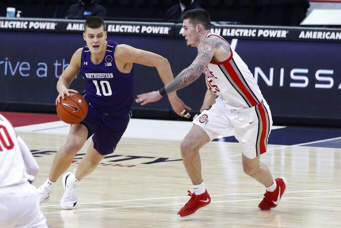 Northwestern's Miller Kopp, left, drives as Ohio State's Kyle Young defends during the second half of an NCAA college basketball game Wednesday, Jan. 13, 2021, in Columbus, Ohio. (AP Photo/Jay LaPrete)