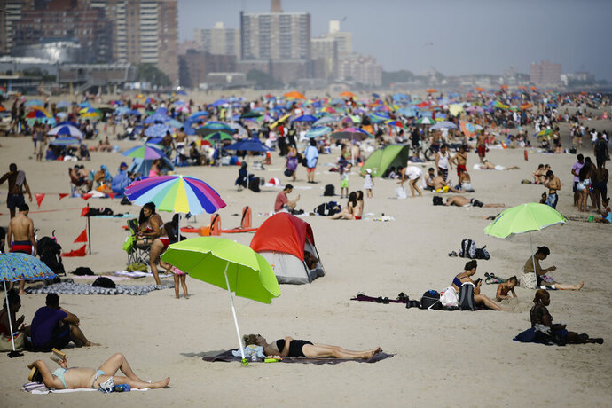 People enjoy the beach at Coney Island Friday, July 19, 2019, in the Brooklyn borough of New York. An excessive heat warning remains in effect throughout the metropolitan area. (AP Photo/Frank Franklin II)