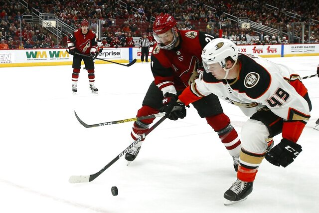 Anaheim Ducks left wing Max Jones (49) battles with Arizona Coyotes center Derek Stepan (21) for the puck as Coyotes left wing Lawson Crouse (67) looks on during the first period of an NHL hockey game Thursday, Jan. 2, 2020, in Glendale, Ariz. (AP Photo/Ross D. Franklin)