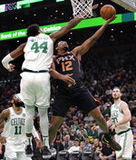 Phoenix Suns forward T.J. Warren (12) drives to the basket against Boston Celtics center Robert Williams (44) during the second half of a basketball game in Boston, Wednesday, Dec. 19, 2018. The Suns defeated the Celtics 111-103. (AP Photo/Charles Krupa)