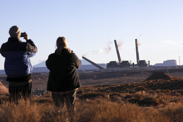 Pat Talbott, right, watches with her son Ted as the first of three structures fall during a controlled demolition collapse at the Navajo Generating Station in Page, Ariz., on Friday, Dec. 18, 2020. The 775-foot (236-meter) structures loomed over the Navajo Generating Station, a 2,250 megawatt plant that closed last year as natural gas became a cheaper alternative for electricity. (Jake Bacon/Arizona Daily Sun via AP)