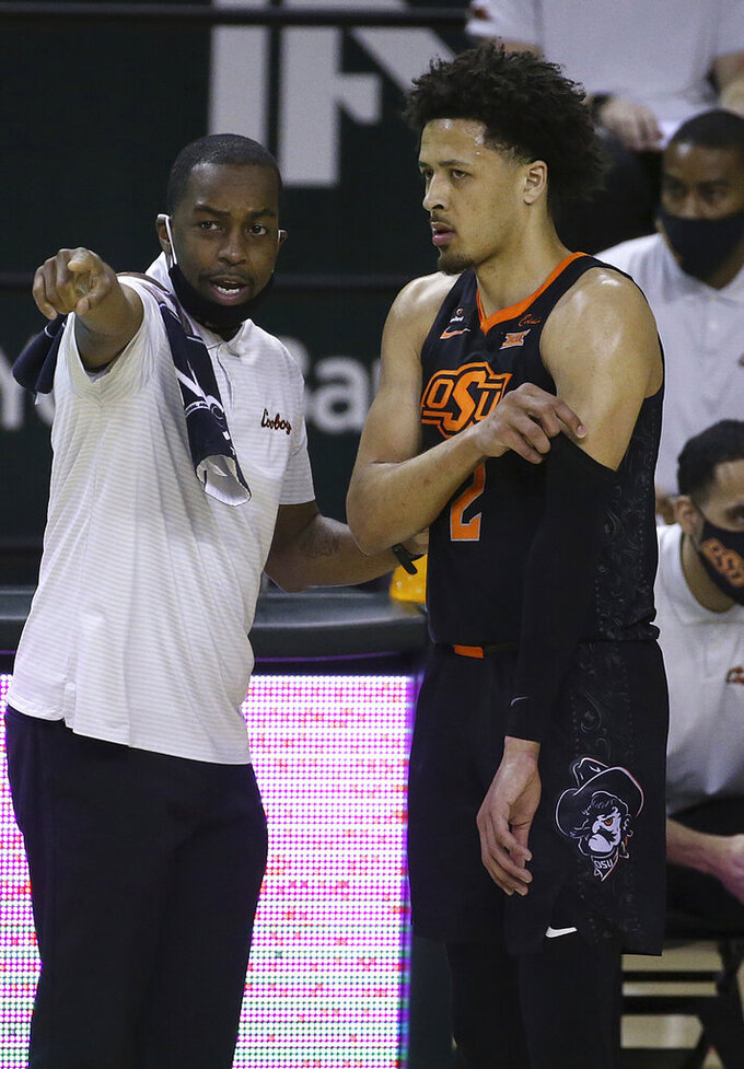 Oklahoma State Mike Boynton directs Oklahoma State guard Cade Cunningham (2) in the first half of an NCAA college basketball game against Baylor, Thursday, March 4, 2021, in Waco, Texas. (AP Photo/Jerry Larson)