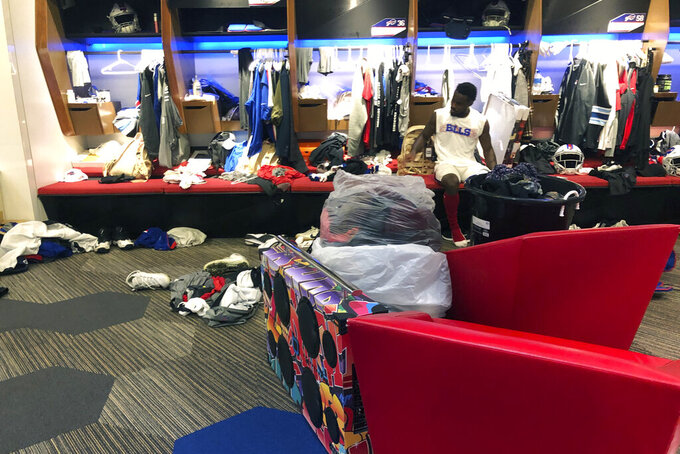 Buffalo Bills NFL football wide receiver Isaiah McKenzie sits at his locker after practice on Monday, Aug. 26, 2019, in Orchard Park, N.Y., with all the worldly possessions he brought to Buffalo stored in front of him. He's got a collection of clothes in one large bucket, and more in two plastic bags, plus an oversized colorful boombox. The third-year player does this as motivation by reminding himself how uncertain his future is with NFL teams making their final cuts by Saturday. And it's also a way of being ready to travel in an instant, should McKenzie get cut by the team. (AP Photo/John Wawrow)