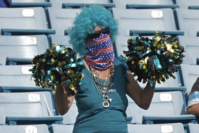 A Jacksonville Jaguars fan cheers during the first half of an NFL football game against the Cleveland Browns, Sunday, Nov. 29, 2020, in Jacksonville, Fla. (AP Photo/Phelan M. Ebenhack)