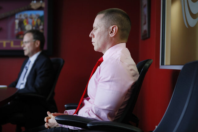 FILE - In this May 21, 2019 file photo Steven Snyder-Hill, right, who claims that a former team doctor for The Ohio State University, Dr. Richard Strauss, now dead, abused him while he was a student sits beside his attorney Scott Elliot Smith, left, during interviews in Columbus, Ohio. Snyder-Hill says he has filed two related complaints with the State Medical Board of Ohio. He says one complaint alleges university President Michael Drake, an ophthalmologist, violated professional ethics and that his school broke laws about sharing public records. He says his other complaint alleges that former student health director Ted Grace mishandled a complaint about misbehavior by Strauss in 1995. Messages seeking comment were left Monday, Jan. 27, 2020 for Ohio State and Grace. Because of confidentiality rules, the medical board won't confirm or comment on complaints unless they result in disciplinary action. (AP Photo/John Minchillo, file)