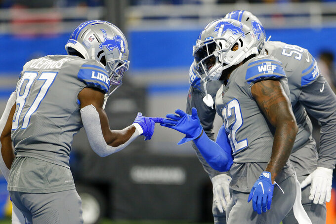 Detroit Lions running back D'Andre Swift (32) celebrates his two-yard touchdown run with Quintez Cephus (87) in the second half of an NFL football game against the Baltimore Ravens in Detroit, Sunday, Sept. 26, 2021. (AP Photo/Duane Burleson)