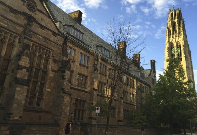 FILE - This Sept. 9, 2016, photo shows Harkness Tower on the campus of Yale University in New Haven, Conn. A 2019 Veterans Day protest in which a student placed red-painted latex gloves over small American flags on campus, has stirred controversy at the university. Senior Casey Odesser says her act was meant as a reminder of the death associated with U.S. military conflicts, not to disrespect members of the armed services. (AP Photo/Beth J. Harpaz, File)