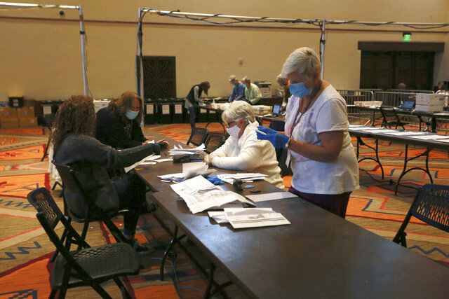FILE - In this Nov. 3, 2020, file photo, election workers sort electronically submitted ballots at the Santa Fe Convention Center on Election Day in Santa Fe, N.M. The state canvassing board has certified Joe Biden's win in New Mexico, delivering the state's five electoral votes to the Democrat. Approval came Tuesday, Nov. 24, 2020, as the board met remotely amid the surging pandemic. (AP Photo/Cedar Attanasio, File)