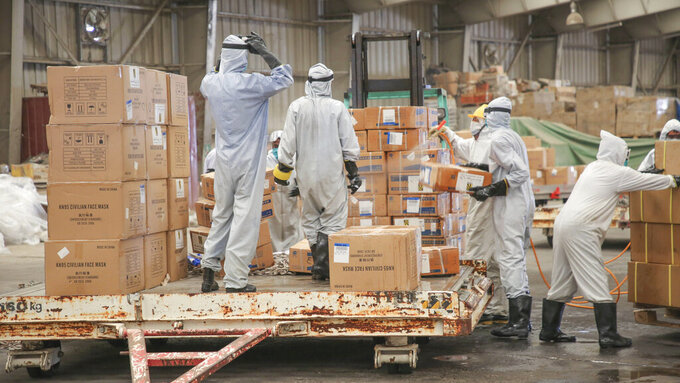 In this Wednesday, June 17, 2020, workers disinfect boxes of medical supplies on arrival at Sanaa International Airport in Sanaa, Yemen. The shipment includes ventilators, coronavirus test kits, PCR machines and personal protective equipment. Organized by the United Nations and private companies, it comes as the UN is facing a funding shortage for its operations in the war-torn country, where officials and medical experts fear the coronavirus could be spreading unchecked due to limited medical facilities. (World Health Organization via AP)