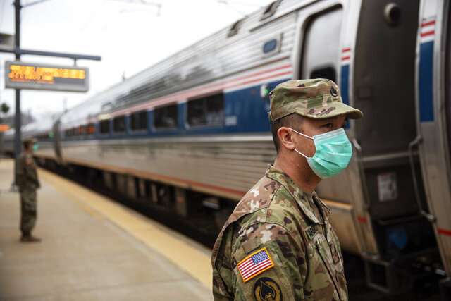 Members of the Rhode Island National Guard look for passengers getting off from a train from New York as it arrives Saturday, March 28, 2020, in Westerly, R.I. States are pulling back the welcome mat for travelers from the New York area, which is the epicenter of the country's coronavirus outbreak, and some say at least one state's measures are unconstitutional. Gov. Gina Raimondo ratcheted up the measures Friday afternoon, announcing she'll also order the state National Guard to go door-to-door in coastal communities starting this weekend to find out whether any of the home's residents have recently arrived from New York and inform them of the quarantine order. (AP Photo/David Goldman)