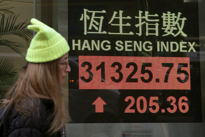 A woman walks past an electronic stock board showing the Hang Seng Index at a bank in Hong Kong, Friday, Jan. 12, 2018. Most Asian stocks markets were mixed Friday, as Wall Street's latest record close and strong oil prices were offset by the strengthening yen, which pressured Japan's Nikkei. (AP Photo/Kin Cheung)