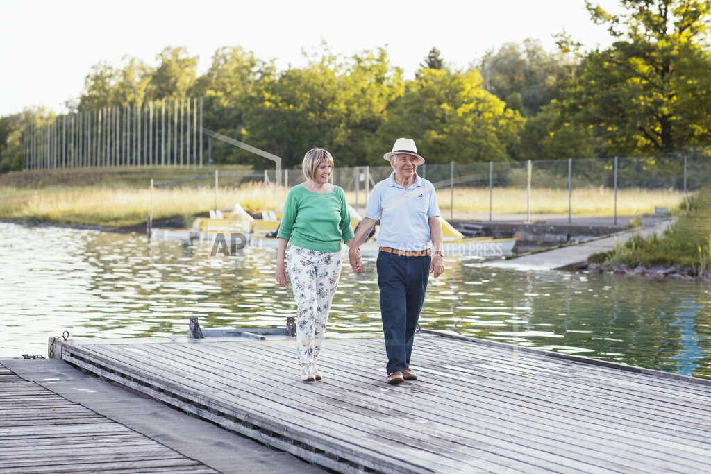 Senior couple holding hands while walking on jetty by lake