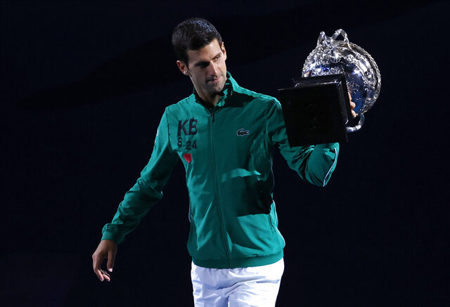 Serbia's Novak Djokovic carries the Norman Brookes Challenge Cup around Rod Laver Arena after defeating Austria's Dominic Thiem in the men's singles final of the Australian Open tennis championship in Melbourne, Australia, early Monday, Feb. 3, 2020. (AP Photo/Dita Alangkara)