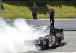 "FILE - In this July 28, 2018, file photo, Kyle Busch celebrates after winning a NASCAR Truck Series auto race in Long Pond, Pa. Busch says, ""Bring it on."" Chase Elliott and Kyle Larson are the latest topflight drivers to accept the challenge of Kevin Harvick, who has offered half of a $100,000 bounty to any Cup Series driver who can beat the versatile Busch in a Truck Series race this year. (AP Photo/Derik Hamilton, File)"