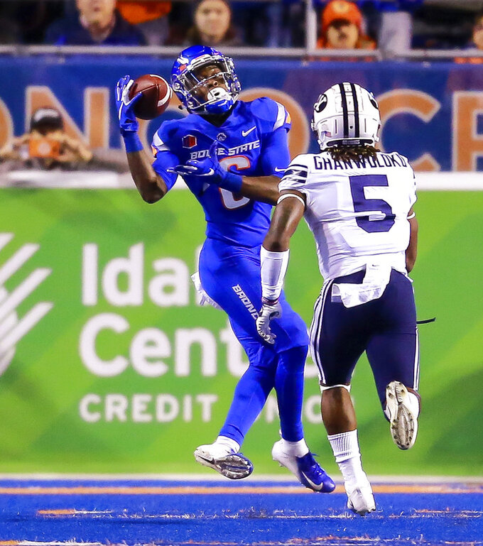 Boise State wide receiver CT Thomas (6) catches the ball on a 31-yard reception in front of BYU defensive back Dayan Ghanwoloku (5) during the first half of an NCAA college football game Saturday, Nov. 3, 2018, in Boise, Idaho. (AP Photo/Steve Conner)