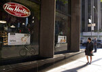 In this Aug. 2, 2017, photo, a woman walks pass a Tim Hortons in Toronto. Restaurant Brands International, the parent company of Burger King and Tim Hortons, reports financial results Monday, Feb. 12, 2018. (Doug Ives/The Canadian Press via AP)