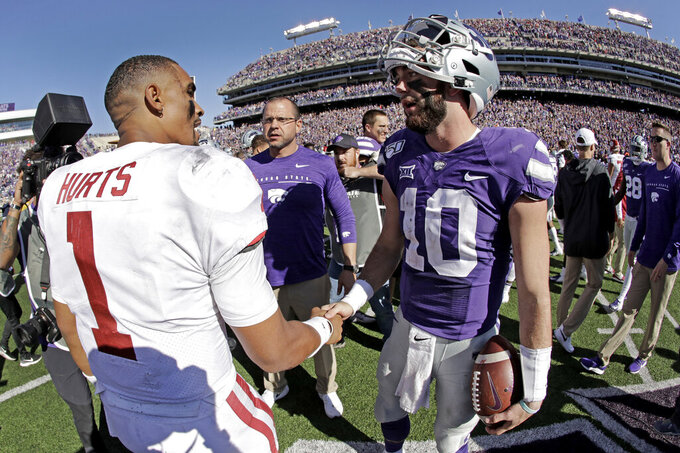 Oklahoma quarterback Jalen Hurts (1) and Kansas State quarterback Skylar Thompson (10) greet each other after their NCAA college football game Saturday, Oct. 26, 2019, in Manhattan, Kan. Kansas State won 48-41. (AP Photo/Charlie Riedel)