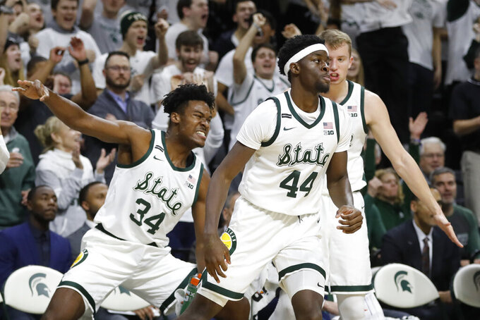 Michigan State forward Julius Marble (34) and forward Thomas Kithier, right, react after a 3-point basket by forward Gabe Brown (44) during the second half of an NCAA college basketball game against Northwestern, Wednesday, Jan. 29, 2020, in East Lansing, Mich. (AP Photo/Carlos Osorio)