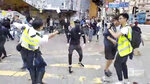 In this image made from video, a police officer, left, prepares to shoot a protester, center, in Hong Kong Monday, Nov. 11, 2019. The police shot the protester as demonstrators blocked subway lines and roads during the Monday morning commute. (Cupid Producer via AP)
