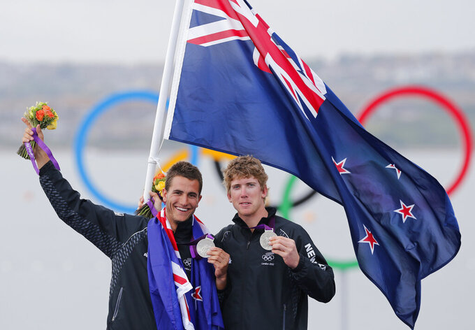 FILE - In this Aug. 8, 2012 file photo Peter Burling and Blair Tuke of New Zealand celebrate their silver medal of the 49er men sailing race at the London 2012 Summer Olympics, in Weymouth and Portland, England. The defending America's Cup champions and Olympic gold medalists have launched a New Zealand team in the SailGP global league. Two of the world's most accomplished sailors, will serve as co-CEOs of the Kiwi team, which will join the circuit during the rescheduled second season next year. (AP Photo/Francois Mori,File)