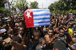 A Papuan activist holds up a separatist 'Morning Star' flag during a rally near the presidential palace in Jakarta, Indonesia, Thursday, Aug. 22, 2019. A group of West Papuan students in Indonesia's capital staged the protest against racism and called for independence for their region. (AP Photo/Dita Alangkara)