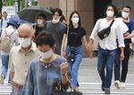 People wearing face masks to protect against the spread of the coronavirus walk on a street in Tokyo Tuesday, July 27, 2021. (AP Photo/Koji Sasahara)