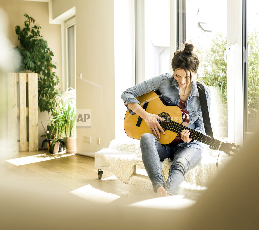 Woman sitting at the window at home playing guitar