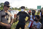 A state trooper speaks to participants in a protest along Interstate 94 in St. Paul, Minn., Wednesday, July 1, 2020. Protesters apparently outraged by the killing of Hachalu Hundessa, a popular singer in Ethiopia, stopped traffic on the interstate during the evening rush hour. Police blocked the entrance ramps to the freeway shortly before 6:30 p.m. Traffic was stopped as the group moved down the interstate. State Patrol spokesman Lt. Gordon Shank said after 8 p.m. the protesters had left the freeway, and no arrests have been made. (Evan Frost/Minnesota Public Radio via AP)