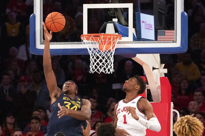West Virginia's Oscar Tshiebwe (34) scores over St. John's Josh Roberts (1) in the second half of an NCAA college basketball game, Saturday, Dec. 7, 2019 in New York. St. John's won 70-68. (AP Photo/Mark Lennihan)