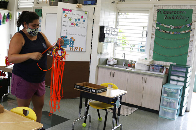 First-grade teacher Shannon Allen prepares a classroom at Aikahi Elementary School in Kailua, Hawaii, Tuesday, July 28, 2020. While Hawaii has one of the lowest rates of cases per capita in the country and many of its schools have open-air campuses, the challenges of returning kids full time to classrooms may still be insurmountable. (AP Photo/Jennifer Sinco Kelleher)