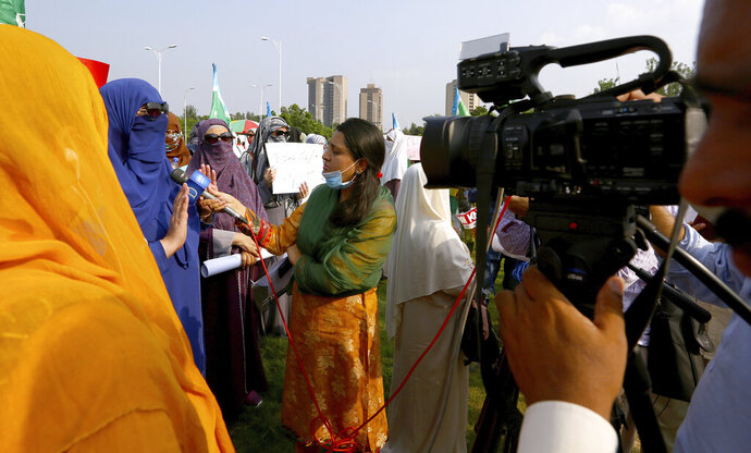 In this Friday, Sept. 11, 2020 photo, Wajiha Khanian, a female journalist from local tv channel Dawn News, interviews during protest, in Islamabad, Pakistan. Social media attacks against Pakistan's women journalists have been vile and vicious, some threatening rape, others even threatening death and the culprits are most often allied to the ruling party, even prompting the Committee to Protect Journalists to issue a statement on Friday condemning the relentless attacks. (AP Photo/Anjum Naveed)