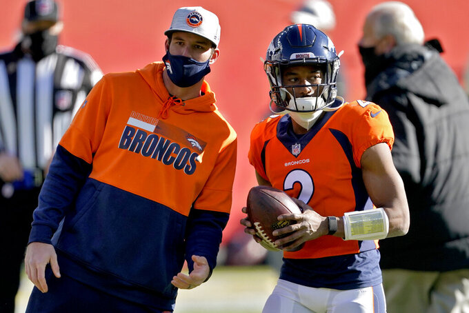 Denver Broncos quarterback Kendall Hinton (2) speaks with Broncos' Offensive Quality Control coach Rob Calabrese prior to an NFL football game against the New Orleans Saints, Sunday, Nov. 29, 2020, in Denver. (AP Photo/Jack Dempsey)