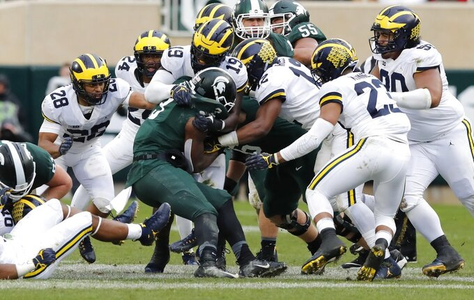 Michigan State running back LJ Scott (3) is stopped by the Michigan defensive line during the second half of an NCAA college football game, Saturday, Oct. 20, 2018, in East Lansing, Mich. (AP Photo/Carlos Osorio)